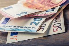 Flera hundra eurosedlar som staplas av värde Europengarbegrepp euroen bemärker reflexion bank repet för anmärkningen för pengar f Arkivbild