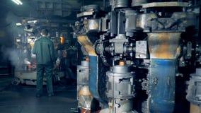 Flera industriella maskiner för framställning och att hårdna av glasflaskor fungerar, och en manlig arbetare är att kontrollera arkivfilmer
