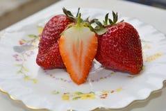 Flera jordgubbar i ett tefat arkivbild