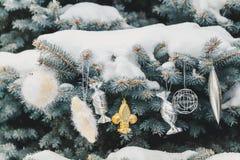 Flera julleksaker väger på snö-täckt filialjul Royaltyfria Bilder