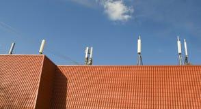 Flera knyter kontakt mobila antenner på ett tak  Arkivfoton