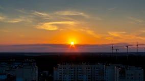 Flera konstruktionskranar på bakgrunden av färgrik solnedgånghimmel royaltyfria bilder