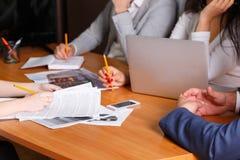 Flera kontorsarbetare, sitter för en intervju och att anteckna ny information och granska dokument royaltyfri fotografi
