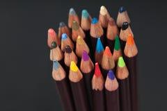 Flera kulöra blyertspennor på mörk bakgrund Royaltyfri Bild