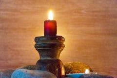 Flera mång--färgade stearinljus tänds och omges av stenar Royaltyfria Foton