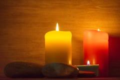 Flera mång--färgade stearinljus tänds och omges av stenar Royaltyfria Bilder