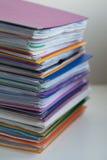 Flera mångfärgade mappar med dokument som staplas i en hög på Arkivfoton
