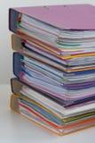 Flera mångfärgade mappar med dokument som staplas i en hög på Arkivbild