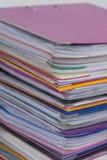Flera mångfärgade mappar med dokument som staplas i en hög på Arkivfoto