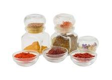 Flera olika kryddor i små glass bunkar och små krus Arkivfoton