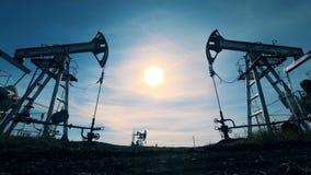 Flera oljautdragningsmaskiner Energi olja, gas, bränsle som pumpar riggen Oljeindustri oljabransch, oljasektor arkivfilmer