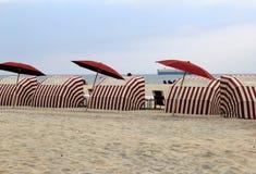 Flera rött och vit gjorde randig cabanas på de sandiga kusterna av stranden Arkivfoton
