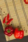 Flera söta mogna röda peppar och varma och pepparärtor på en napk Royaltyfri Fotografi