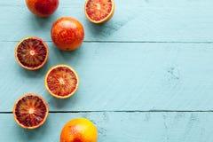 Flera sangviniska apelsiner på blå träbakgrund Royaltyfri Bild