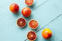 Flera sangviniska apelsiner på blå träbakgrund Royaltyfri Foto