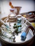 Flera små medicinflaskor och att ge första erfarenhet prövkopian i ett metallmagasin fotografering för bildbyråer