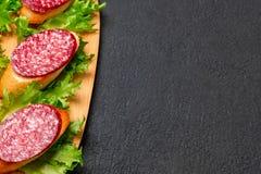 Flera smörgåsar med korven och salami och sås på ett svart bräde, bakgrund med copyspace royaltyfria foton