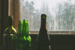 Flera tomglas av alkohol nära det smutsiga fönstret Selektivt fokusera Alkoholism, berusning, ensamhet och fördjupning royaltyfria foton