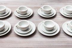 Flera vita koppar och tefat på grå färgbrunttabellen Arkivfoton