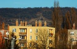 Flerbostadshus framme av ett berg arkivbilder