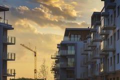 Flerbostadshus under konstruktion med kranen på solnedgånghimmel som möter stopptidbegrepp Arkivfoton