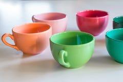 Flerfärgad kopp på en tabell Royaltyfria Bilder