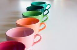 Flerfärgad kopp på en whietabell Arkivbilder