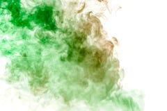 Flerfärgad tjock rök, exponerad av kulört i gräsplan och rött ljus mot en vit isolerad bakgrund som svetsas med klubbor och royaltyfria bilder