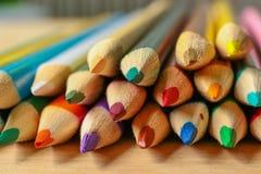 Flerfärgade blyertspennor på träbakgrund royaltyfria foton