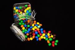 Flerfärgade godisar i den glass krusisolaten på svart bakgrund royaltyfri fotografi