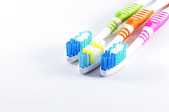 Flerfärgade tandborstar på vit bakgrund Fotografering för Bildbyråer