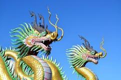 Flerfärgat av två kinesiska drakestatyer mot blå himmel fotografering för bildbyråer