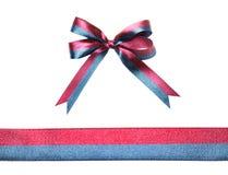 Flerfärgat blått-rött tygband och pilbåge som isoleras på en vit bakgrund Royaltyfri Bild