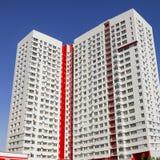 Flervånings- ny modern hyreshus mot den blåa himlen Stilfullt bosatt flerbostadshus blocket byggde delar nytt Arkivfoto