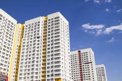 Flervånings- ny modern hyreshus mot den blåa himlen Stilfullt bosatt flerbostadshus blocket byggde delar nytt Arkivbilder