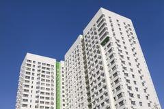 Flervånings- ny modern hyreshus mot den blåa himlen Stilfullt bosatt flerbostadshus blocket byggde delar nytt Royaltyfria Bilder