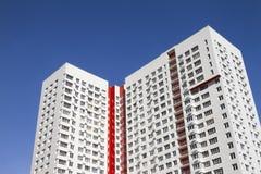 Flervånings- ny modern hyreshus mot den blåa himlen Stilfullt bosatt flerbostadshus blocket byggde delar nytt Royaltyfri Fotografi