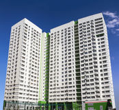 Flervånings- ny modern hyreshus mot den blåa himlen Stilfullt bosatt flerbostadshus blocket byggde delar nytt Arkivbild