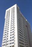 Flervånings- ny modern hyreshus mot den blåa himlen Stilfullt bosatt flerbostadshus blocket byggde delar nytt Royaltyfri Bild