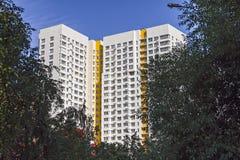 Flervånings- ny modern hyreshus som omges mot den blåa himlen Stilfullt bosatt flerbostadshus Arkivbild