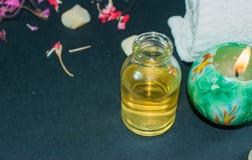 Fles aromaetherische olie met kaars, bloemblaadjebloemen Royalty-vrije Stock Foto's