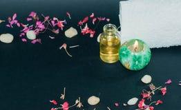 Fles aromaetherische olie met kaars, bloemblaadjebloemen Royalty-vrije Stock Fotografie