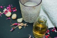 Fles aromaetherische olie met kaars, bloemblaadjebloemen Royalty-vrije Stock Foto