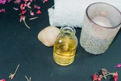 Fles aromaetherische olie met kaars, bloemblaadjebloemen Stock Fotografie