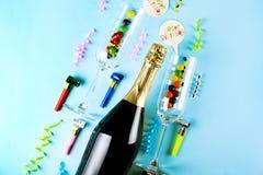 Fles champagne, paar fluitglazen, wimpels, kaarsen & andere partijeigenschappen op heldere roze document achtergrond toespraak royalty-vrije stock afbeelding