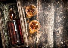 fles cognac in een oude doos royalty-vrije stock afbeelding