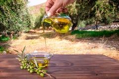 Fles die Kretenzische extra eerste persing in een kom op houten lijst gieten bij een olijfboomgebied Royalty-vrije Stock Foto's