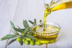 Fles die maagdelijke extra olijfolie in een kom gieten Stock Afbeelding