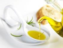 Het maagdelijke olijfolie gieten in een lepel royalty-vrije stock afbeelding