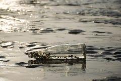 Fles die op een strand liggen stock foto's